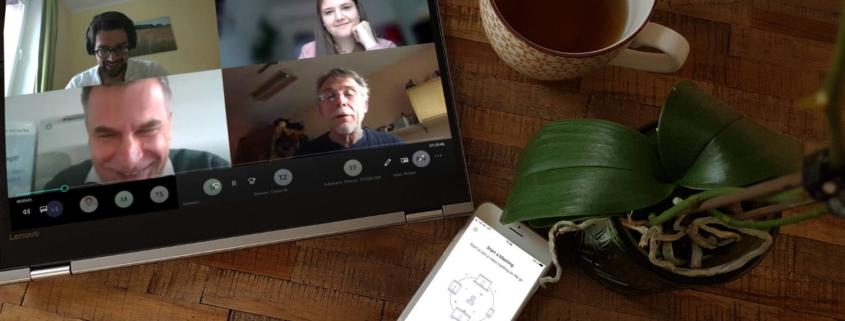 Schreibtisch mit Tablet auf dem ein Online Meeting mit 4 Personen zu seheh ist, ein Handy mit der Aufschrift Meeting starten, eine Teetasse und ein Teil einer Orchidee