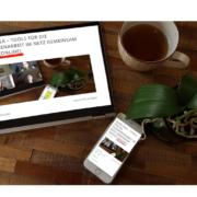 Tablet und Iphone, die eine Online Veranstaltung von quer.kraft zeigen und auf einem Holzschreibtisch liegen