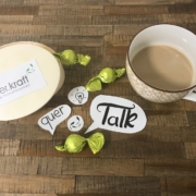 Box mit quer.kraft logo, drei Pralinen, Sprechblasen mit den Wörtern quer und Talk, Kaffeetasse auf braunem Hintergrund