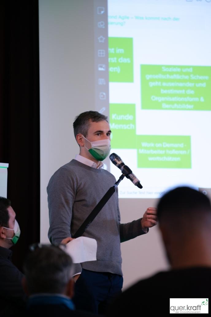 Zusammenfassung der Workshopergebnisse durch einen Moderator auf der Bühne
